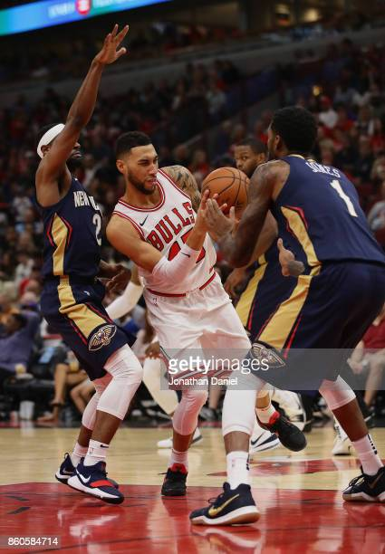 Denzel Valentine of the Chicago Bulls moves between Ian Clark and Perry Jones of the New Orleans Pelicans during a preseason game at the United...