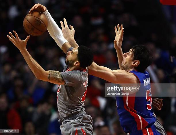 Denzel Valentine of the Chicago Bulls rebounds in front of Boban Marjanovic of the Detroit Pistons at the United Center on December 19 2016 in...
