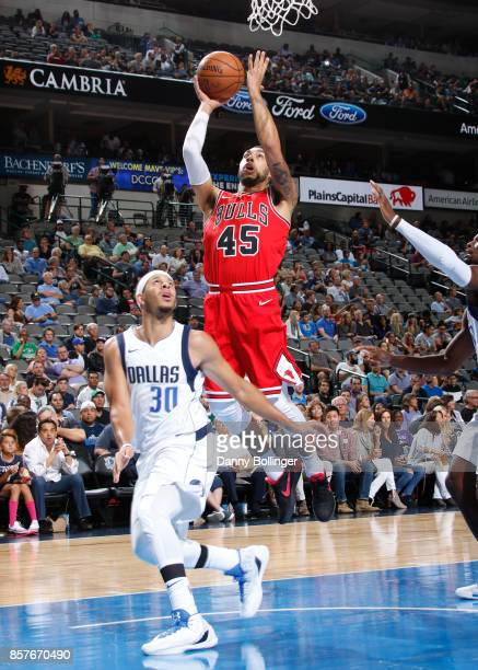 Denzel Valentine of the Chicago Bulls shoots the ball against Seth Curry of the Dallas Mavericks during the preseason game on October 4 2017 at the...
