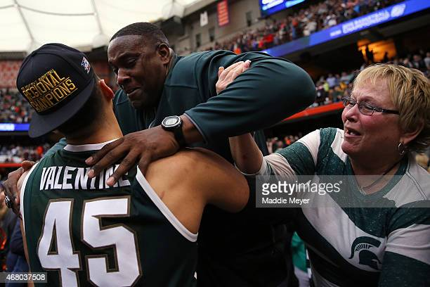 Denzel Valentine of the Michigan State Spartans celebrates with his parents Carlton and Kathy after defeating the Louisville Cardinals 76 to 70 in...