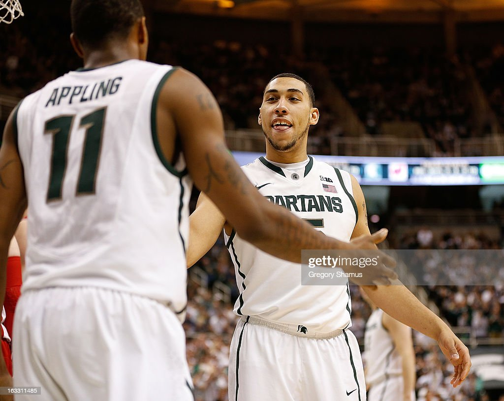 Denzel Valentine #45 of the Michigan State Spartans celebrates with Keith Appling #11 during the second half while playing the Wisconsin Badgers at the Jack T. Breslin Student Events Center on March 7, 2013 in East Lansing, Michigan. Michigan State won the game 58-43.