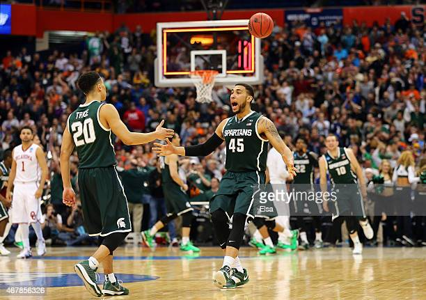 Denzel Valentine of the Michigan State Spartans celebrates with teammate Travis Trice after defeating the Oklahoma Sooners 62 to 58 during the East...