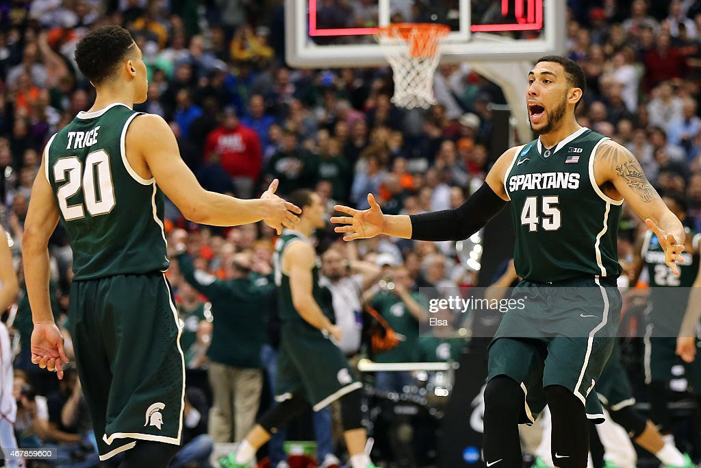 <a gi-track='captionPersonalityLinkClicked' href=/galleries/search?phrase=Denzel+Valentine&family=editorial&specificpeople=9980674 ng-click='$event.stopPropagation()'>Denzel Valentine</a> #45 of the Michigan State Spartans celebrates with teammate <a gi-track='captionPersonalityLinkClicked' href=/galleries/search?phrase=Travis+Trice&family=editorial&specificpeople=8624391 ng-click='$event.stopPropagation()'>Travis Trice</a> #20 after defeating the Oklahoma Sooners 62 to 58 during the East Regional Semifinal of the 2015 NCAA Men's Basketball Tournament at the Carrier Dome on March 27, 2015 in Syracuse, New York.