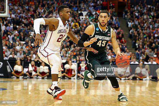 Denzel Valentine of the Michigan State Spartans drives against Buddy Hield of the Oklahoma Sooners during the East Regional Semifinal of the 2015...