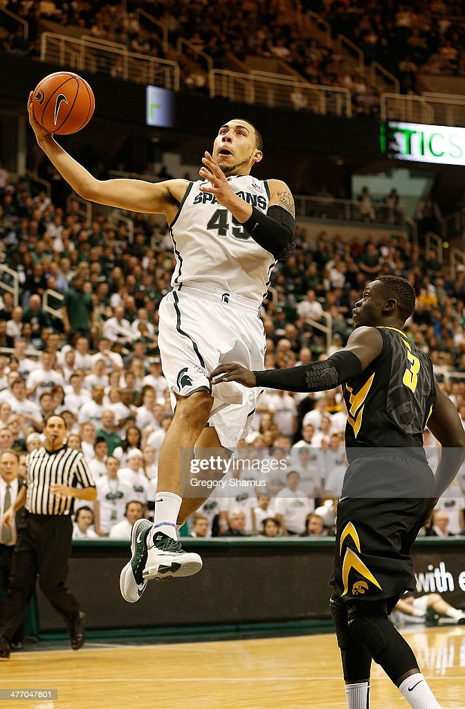 Denzel Valentine #45 of the Michigan State Spartans drives to the basket past Peter Jok #3 of the Iowa Hawkeyes during the second half at the Jack T. Breslin Student Events Center on February 6, 2014 in East Lansing, Michigan. Michigan State won the game 86-76.