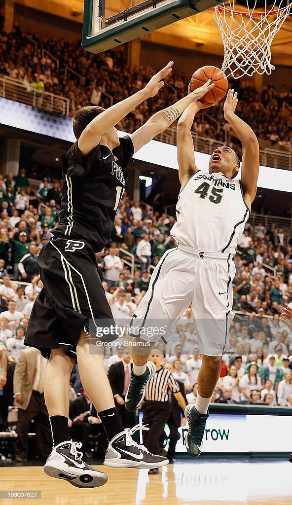 Denzel Valentine #45 of the Michigan State Spartans gets a second half shot off over Donnie Hale #15 of the Purdue Boilermakers at the Jack T. Breslin Student Events Center on January 5, 2013 in East Lansing, Michigan. Michigan State won the game 84-61.