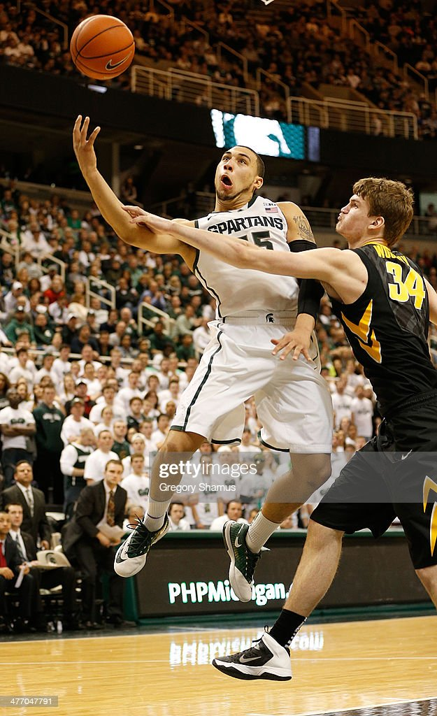Denzel Valentine #45 of the Michigan State Spartans gets fouled on a second half shot attempt by Adam Woodbury #34 of the Iowa Hawkeyes at the Jack T. Breslin Student Events Center on February 6, 2014 in East Lansing, Michigan. Michigan State won the game 86-76.