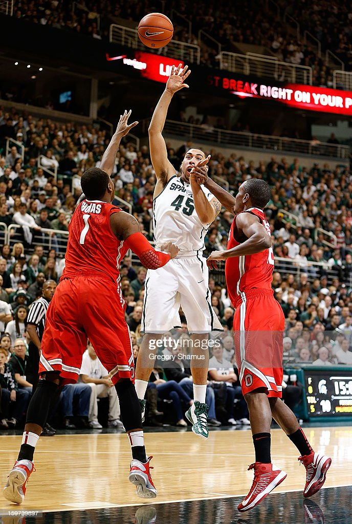 Denzel Valentine #45 of the Michigan State Spartans puts up a first-half shot against Deshaun Thomas #1 and Sam Thompson #12 of the Ohio State Buckeyes at the Breslin Center on January 19, 2013 in East Lansing, Michigan. Michigan State won the game 59-56.