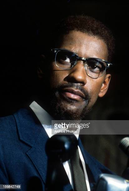 Denzel Washington unshaved face and wearing glasses in a scene from the film 'Malcom X' 1992