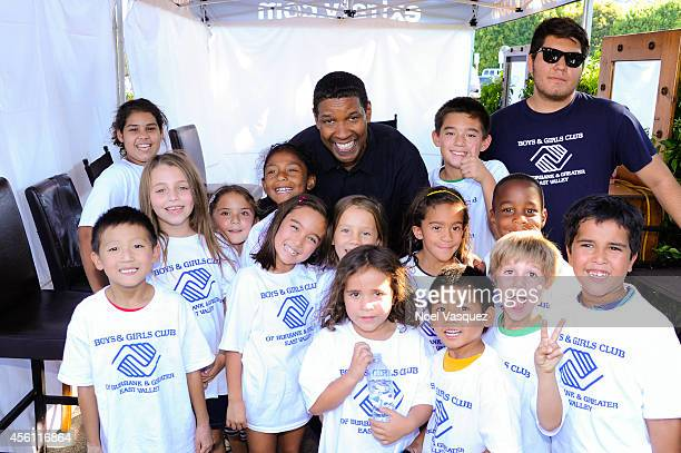 Denzel Washington poses with children from the Boys and Girls Club 'Extra' at Universal Studios Hollywood on September 25 2014 in Universal City...