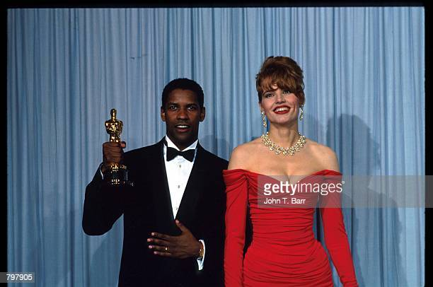 Denzel Washington stands with Gina Davis during the 62nd Academy Awards ceremony March 26 1990 in Los Angeles CA Washington received an Oscar for...
