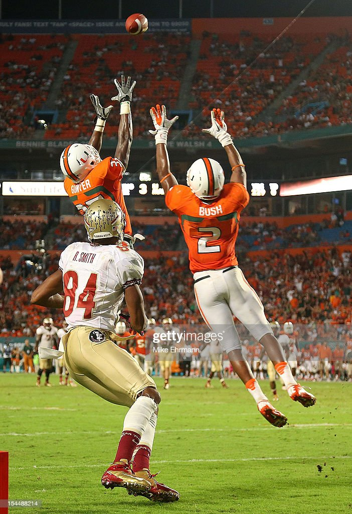 Deon Bush #2 and Ladarius Gunter #37 of the Miami Hurricanes go up for a catch against Rodney Smith #84 of the Florida State Seminoles during a game at Sun Life Stadium on October 20, 2012 in Miami Gardens, Florida.