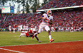Deon Cain of the Clemson Tigers catches as touchdown pass as Jack Tocho of the North Carolina State Wolfpack dives to try to stop him during their...