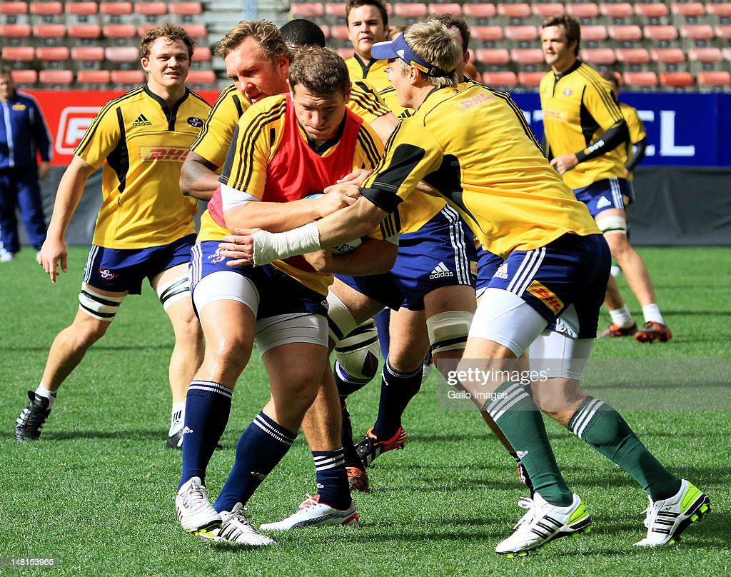 Deon Carstens is tackled by Andries Bekker and Jean de Villiers during a DHL Stormers training session at DHL Newlands on July 11 2012 in Cape Town...