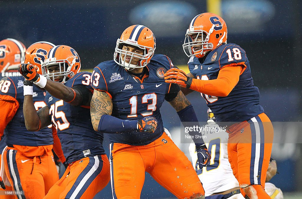 Deon Goggins #13, Siriki Diabate #18 and Dyshawn Davis #35 of the Syracuse Orange celebrate on the field during the game against the West Virginia Mountaineers during the New Era Pinstripe Bowl at Yankee Stadium on December 29, 2012 in the Bronx borough of New York City.