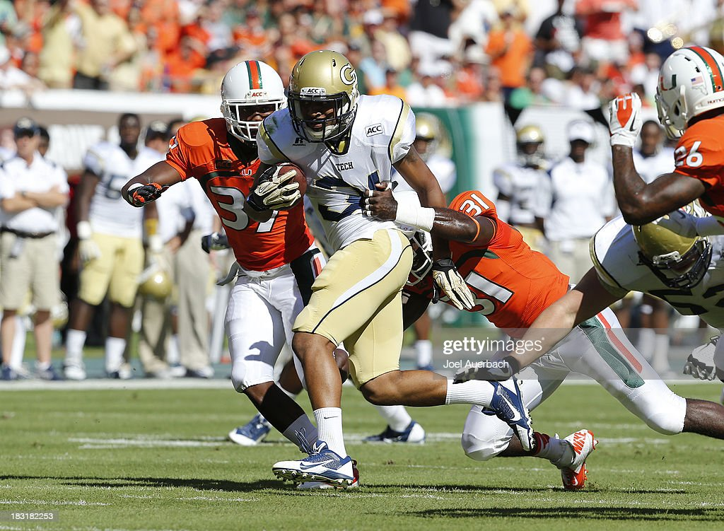 Deon Hill #31 of the Georgia Tech Yellow Jackets runs with the ball past the attempted tackle by Tyrone Cornileus #31 of the Miami Hurricanes on October 5, 2013 at Sun Life Stadium in Miami Gardens, Florida. The Hurricanes defeated the Yellow Jackets 45-30.
