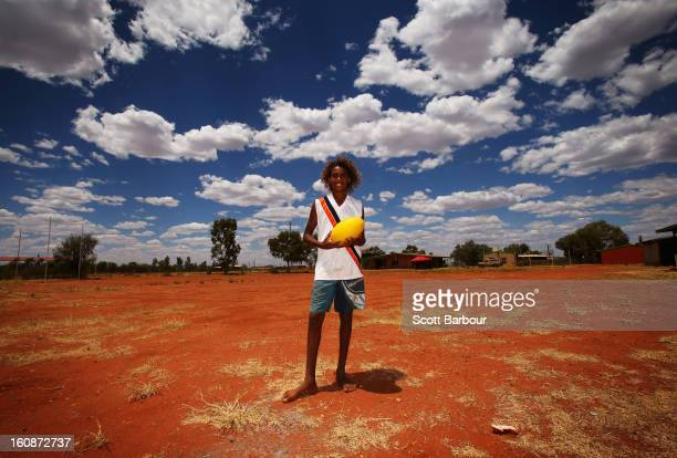 YUENDUMU AUSTRALIA FEBRUARY Deon Lechleitner poses with an Australian rules football as members of the Indigenous All Stars visit Yuendumu School in...