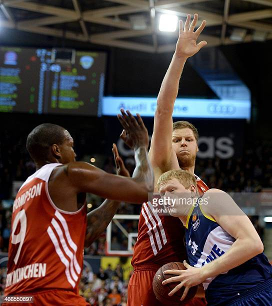 Deon Thompson and John Bryant of Muenchen challenge Philipp Neumann of Oldenburg during the match between FC Bayern Muenchen and EWE Baskets...