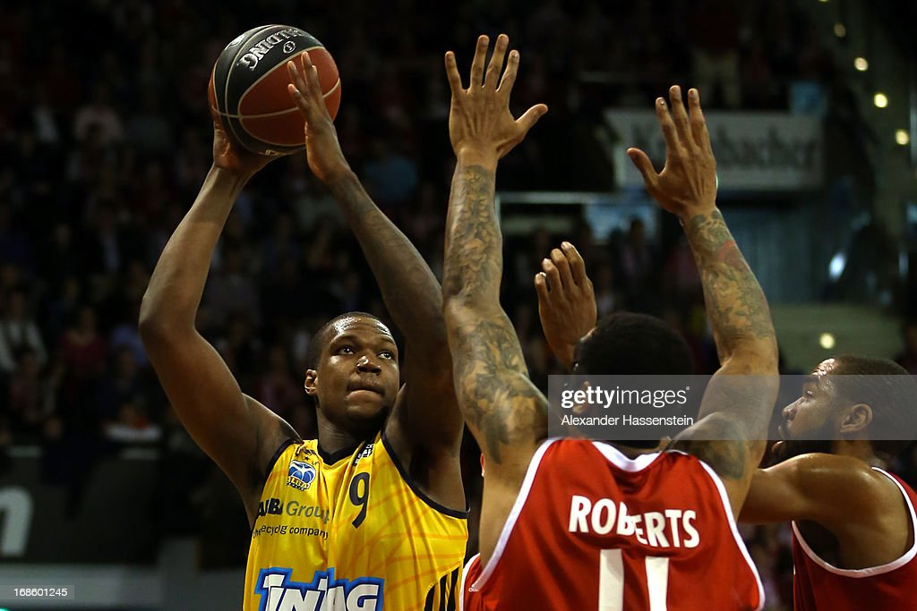 Deon Thompson of Berlin shoots against Lawrence Roberts of Muenchen and his team mate Brandon Thomas (R) during Game 3 of the quarterfinals of the Beko Basketball Playoffs between FC Bayern Muenchen and ALBA Berlin at Audi-Dome on May 12, 2013 in Munich, Germany.
