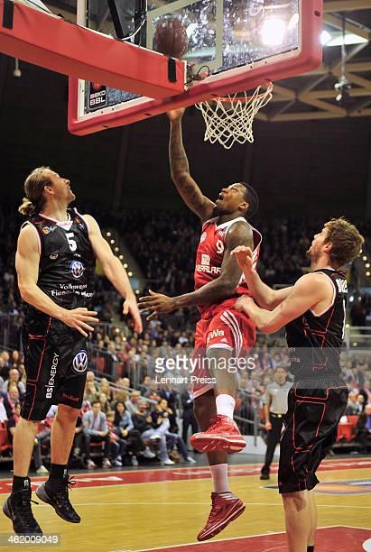 Deon Thompson of Muenchen scores against Robert Kulawick and Aaron Doornekamp of Braunschweig during the Beko Basketball Bundesliga match between FC...
