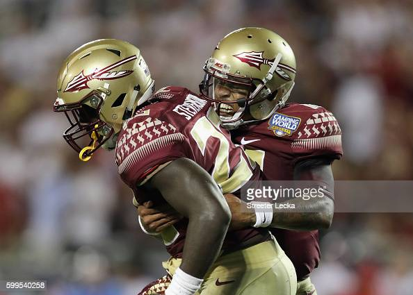 Deondre Francois celebrates with Freddie Stevenson after throwing a touchdown pass to Ryan Izzo of the Florida State Seminoles during the third...