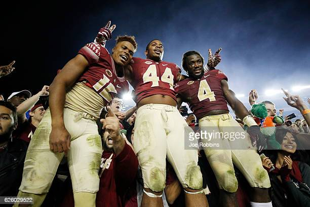 Deondre Francois DeMarcus Walker and Dalvin Cook of the Florida State Seminoles celebrate after the game against the Florida Gators at Doak Campbell...
