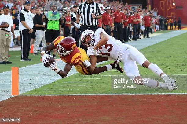 Deontay Burnett of the USC Trojans dives into the end zone to score a second quarter touchdown as Alijah Holder of the Stanford Cardinal attempts to...