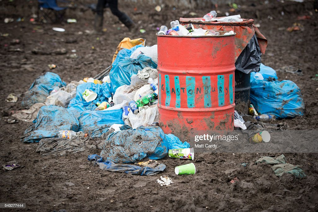 Departing festival goers pass rubbish left behind at the Glastonbury Festival 2016 at Worthy Farm, Pilton on June 26, 2016 near Glastonbury, England. The Festival, which Michael Eavis started in 1970 when several hundred hippies paid just £1, now attracts more than 175,000 people.