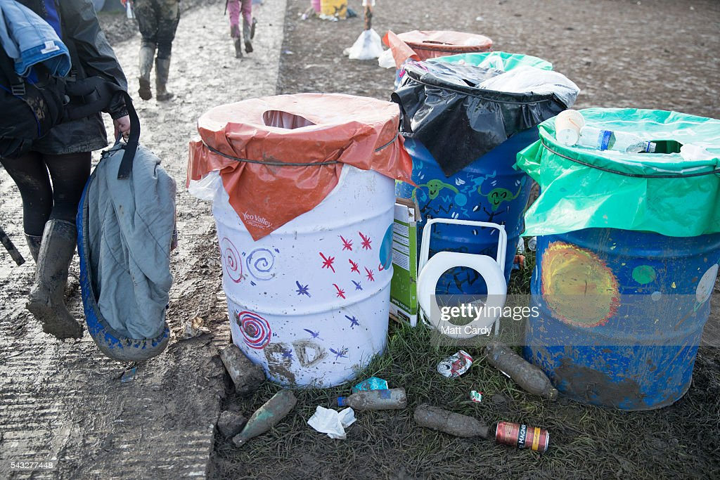Departing festival goers pass rubbish left behind including a portable loo seat at the Glastonbury Festival 2016 at Worthy Farm, Pilton on June 26, 2016 near Glastonbury, England. The Festival, which Michael Eavis started in 1970 when several hundred hippies paid just £1, now attracts more than 175,000 people.