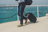 Departing with my suitcase. Man walks on a pier carrying a suitcase. tourist pulls his suitcase on wheels on pier against the sea. The concept of sea travel to exotic countries and beautiful Islands