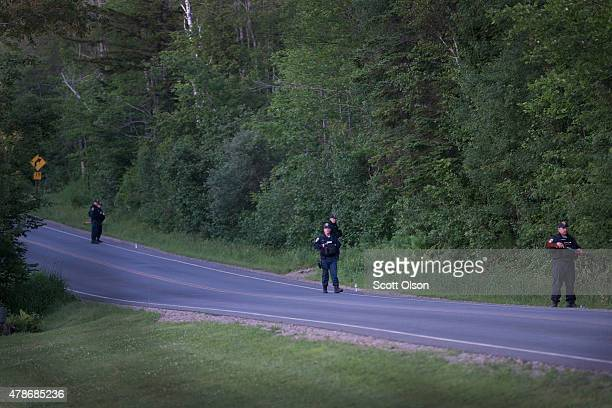 Department of Correction officers stand guard along a wood line near the scene where escaped convict Richard Matt was shot and killed by law...