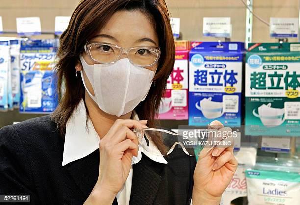 Department store sales clerk Hiromi Konishi displays antihayfever mask and goggles at Toyko's Mitsukoshi department store 21 February 2005 Japanese...