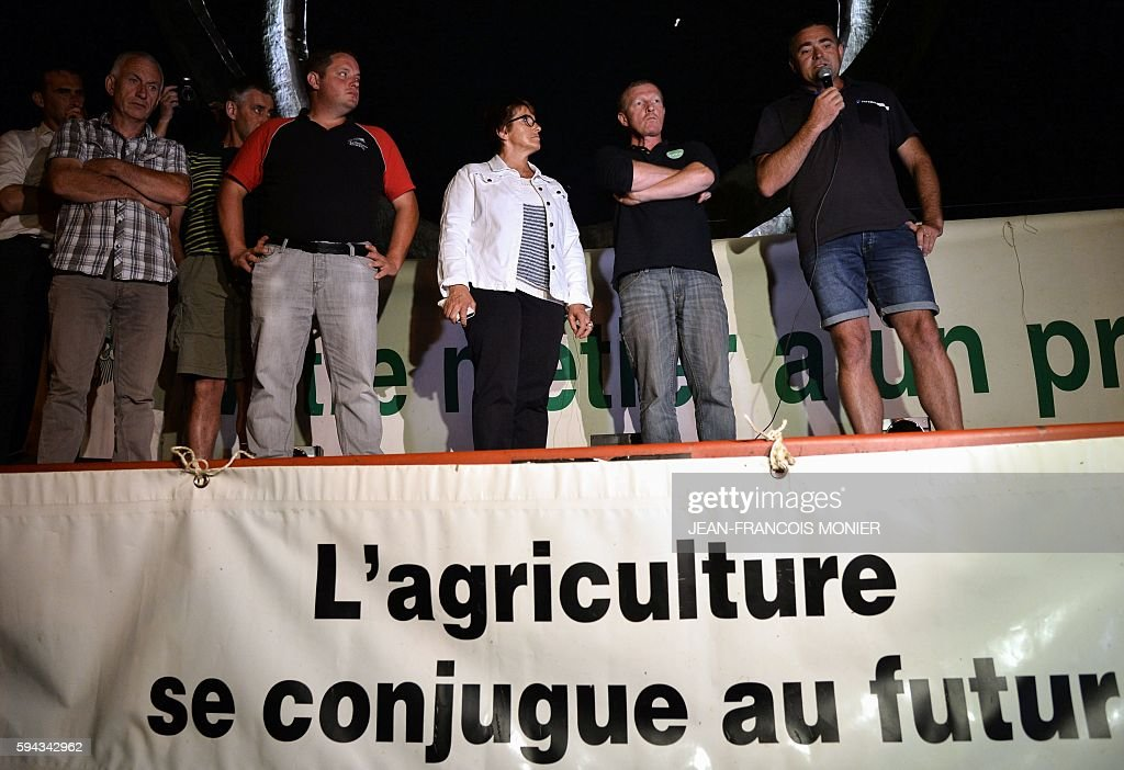 Departmental President of the Milk Producers National Federation Florent Renaudier speaks next to milk producers blocking an access to the Lactalis...