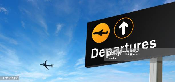Panneau des départs et avion sur le ciel