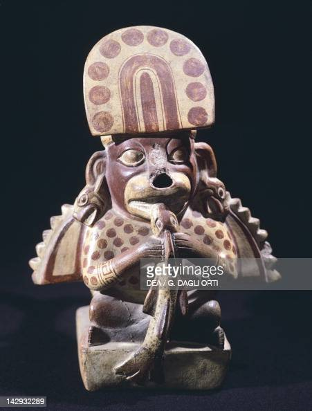 Depiction of a man with a dog's head eating a fish Pottery artifact originating from Peru PreInca Mochica Civilization 4th9th Century Lima Museo...