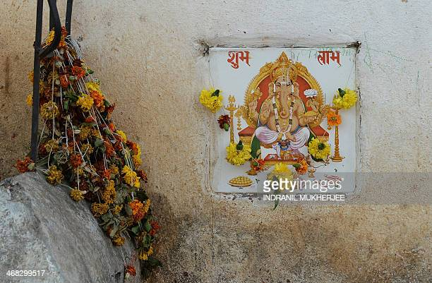 A depiction of the Hindu god Lord Ganesha is seen surrounded by flowers on a wall in Mumbai on February 10 2014 AFP PHOTO/Indranil MUKHERJEE