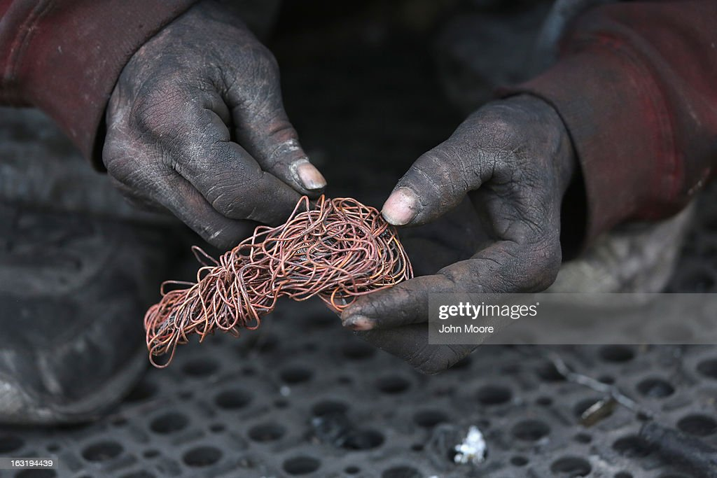 Deported immigrant Jorge Dariel sorts copper he stripped from wiring that he found at the Tirabichi landfill on March 5, 2013 in Nogales, Mexico. He said he had been working in construction in Arizona for about 3 years when he was apprehended by U.S Customs and Border Protection agents and sent back to Mexico. About 30 families, including Jorge, live at the dump, searching for recyclables to sell for a living. He and others have received aid from the non-profit Home of Hope and Peace, which plans to expand it's assistance to the dump's impoverished populace in the future.