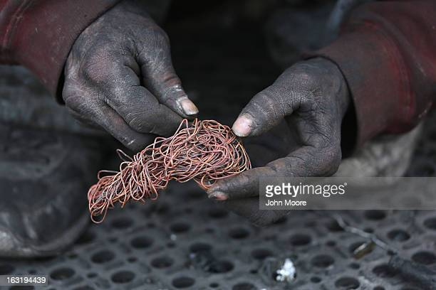 Deported immigrant Jorge Dariel sorts copper he stripped from wiring that he found at the Tirabichi landfill on March 5 2013 in Nogales Mexico He...
