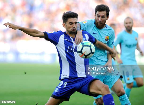 Deportivo Alaves' midfielder Enzo Fernandez vies with Barcelona's Argentinian forward Lionel Messi during the Spanish league football match Deportivo...