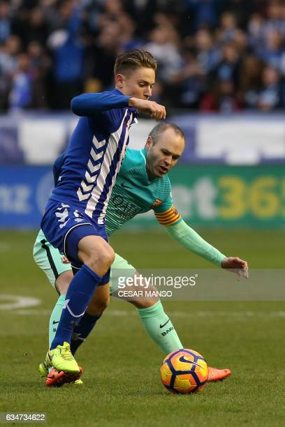 Deportivo Alaves midfielder Marcos Llorente vies with Barcelona's midfielder Andres Iniesta during the Spanish league football match Deportivo Alaves...