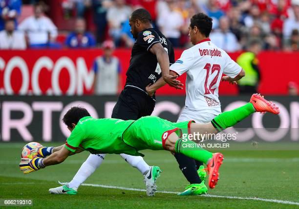 Deportivo La Coruna's Argentinian goalkeeper German Dario Lux dives for the ball beside Deportivo La Coruna's Brazilian defender Sidnei and Sevilla's...
