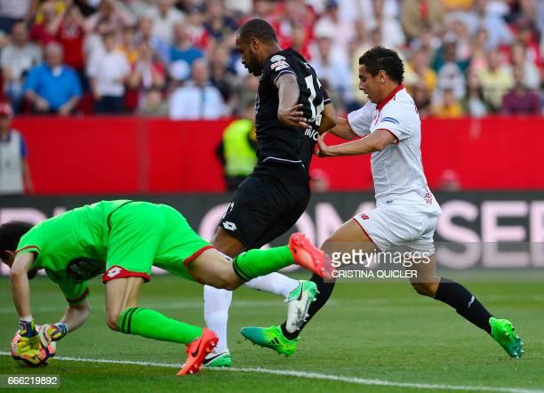 Deportivo La Coruna's Argentinian goalkeeper German Dario Lux secures the ball beside Deportivo La Coruna's Brazilian defender Sidnei and Sevilla's...