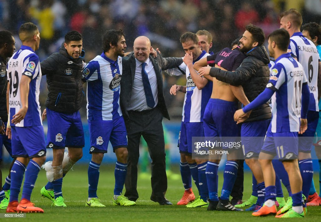 Deportivo La Coruna's coach Pepe Mel (C) celebrates with his players at the end of the Spanish league footbal match RC Deportivo de la Coruna vs FC Barcelona at the Municipal de Riazor stadium in La Coruna on March 12, 2017. /