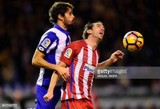 Deportivo La Coruna's defender Alejandro Arribas vies with Atletico Madrid's Uruguayan defender Diego Godin during the Spanish league football match...