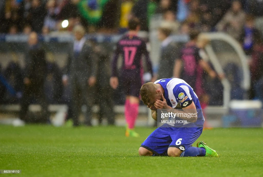 Deportivo La Coruna's defender Raul Albentosa kneels on the field as he celebrates at the end of the Spanish league footbal match RC Deportivo de la Coruna vs FC Barcelona at the Municipal de Riazor stadium in La Coruna on March 12, 2017. /