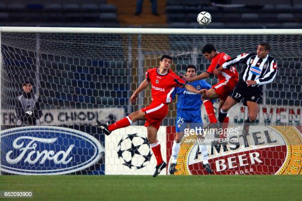 Deportivo La Coruna's goalkeeper Juanmi looks on as teammates Cesar and Nouredine Naybet jump for a header with Juventus's David Trezeguet