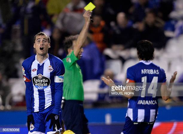 Deportivo La Coruna's midfielder Alex Bergantinos reacts as referee David Fernandez shows a yellow card during the Spanish league football match RC...