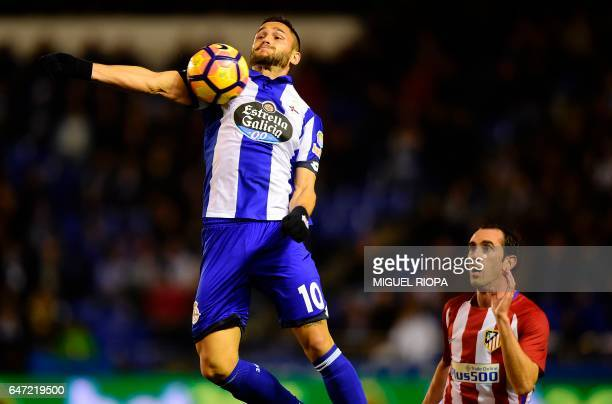 Deportivo La Coruna's Romanian forward Florin Andone controls the ball past Atletico Madrid's Uruguayan defender Diego Godin during the Spanish...