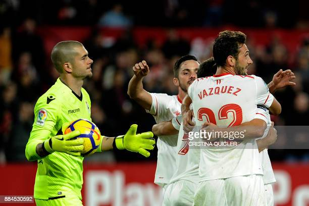 Deportivo La Coruna's Spanish goalkeeper Ruben reacts as Sevilla's French forward Wissam Ben Yedder celebrates with teammates after scoring a goal...