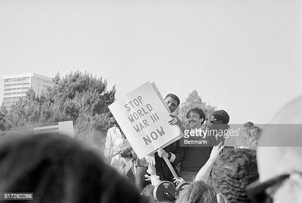 Deposed heavyweight boxing champion Cassius Clay peers around a 'Stop WorldWar III' peace picket sign held by unidentified picketer after Clay...